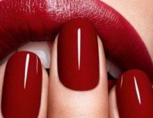 Алые ногти на фоне губ