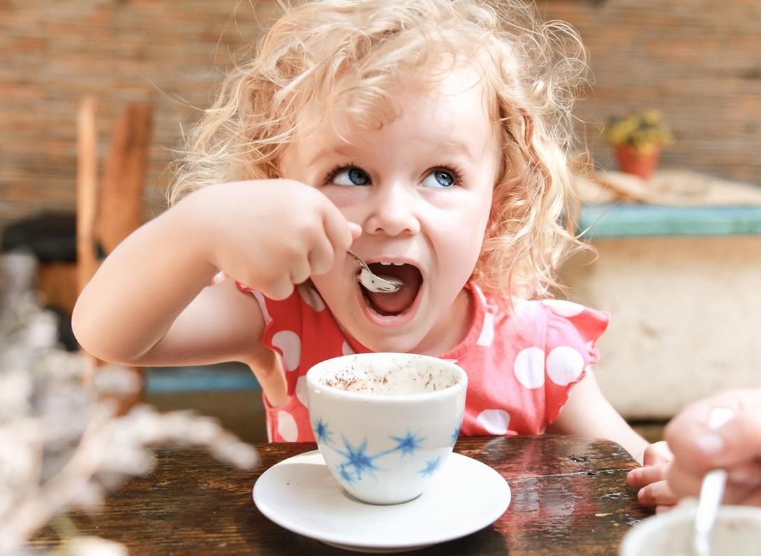 Ребенок пьет напиток из ложки